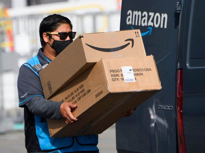 FILE: An Amazon.com Inc. delivery driver carries boxes into a van outside of a distribution facility on Feb. 2, 2021 in Hawthorne, Cali. /